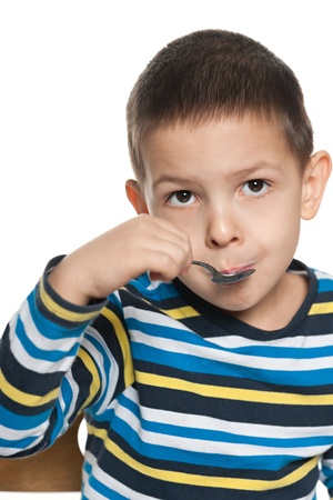 one boy only: A serious little boy eats with a spoon his breakfast