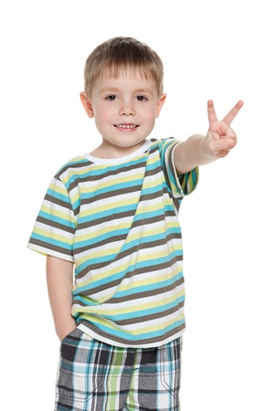 A portrait of a smiling young boy shows victory sign on the white background photo