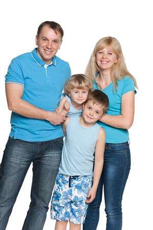small group of people: Mother, father and two sons are standing together on the white background