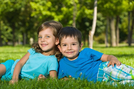brothers and sisters: A boy and a girl are resting on the green grass in the sunny summer day Stock Photo