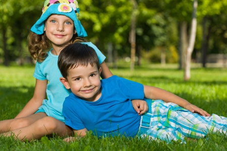 A boy and a girl are resting on the green grass in the summer park photo