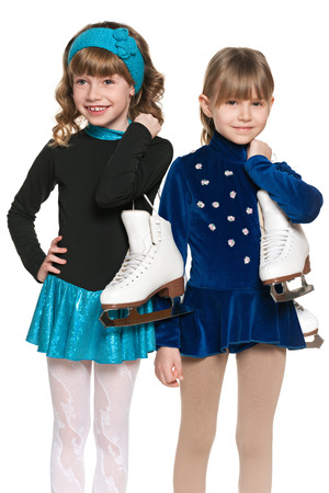 Two smiling little girls with skates on the white background photo