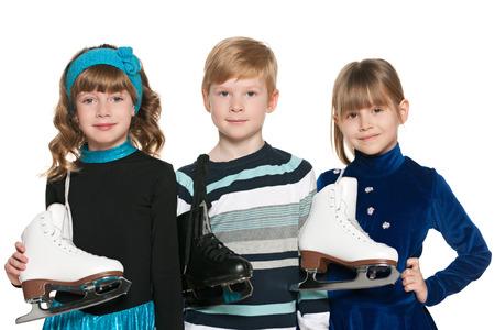 patinar: Tres niños sonrientes con patines sobre el fondo blanco