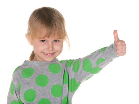A closeup portrait of a cheerful little girl  with her thumb up on the white background photo