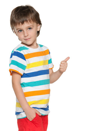 fashion boy: A smiling fashion little boy in blue shirt holding his thumb up and back on the white background