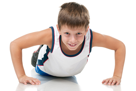 A handsome athletic young boy is pushing up on the white background photo