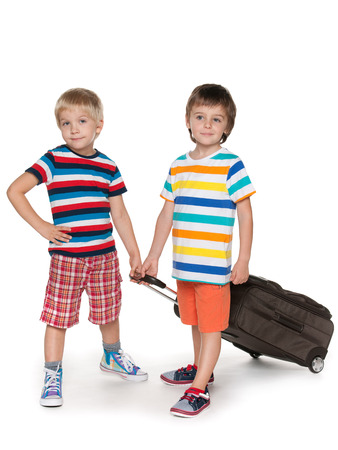 A little boys with a suitcase are standing together on the white background photo