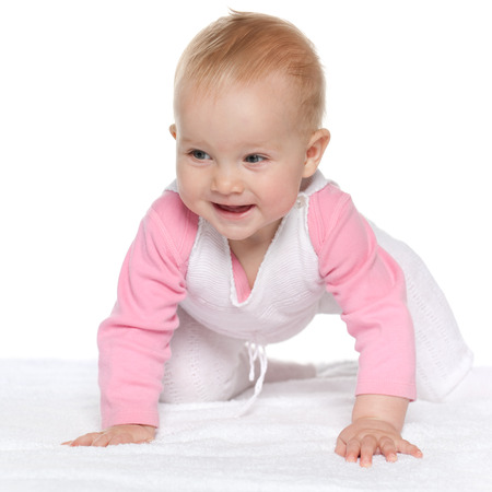 A smiling baby girl is crawling on the white towel photo