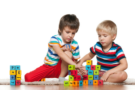 Two cute boys are playing with blocks on the floor photo