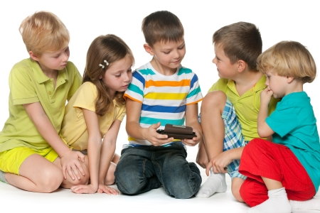 Group of five little children are playing with a new gadget photo