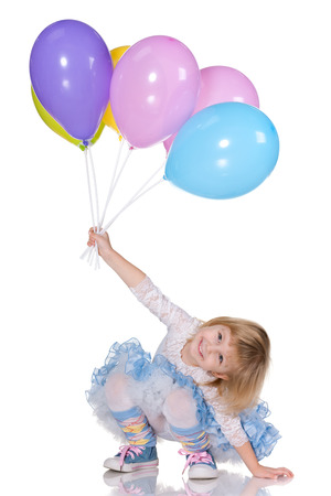 A cheerful little girl is playing with balloons on the white background photo