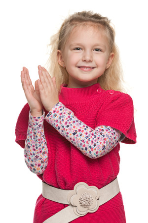 A closeup portrait of a cheerful little girl that applauds