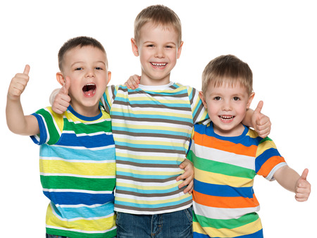 Three joyful boys are standing together on the white background