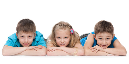 A portrait of a group of three children lying on the white background photo