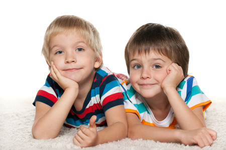 Two little boys are lying together on the white carpet photo