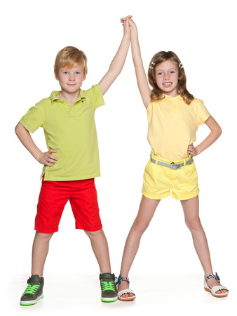 Two cheerful children a standing together and hold their hands up on a white background photo