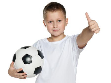 pelota de futbol: Un muchacho sonriente con bal�n de f�tbol tiene su dedo pulgar hacia arriba en el fondo blanco Foto de archivo