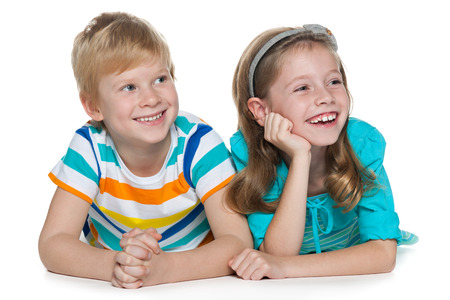 aside: Two cheerful children are lying together and looking aside on the white background Stock Photo