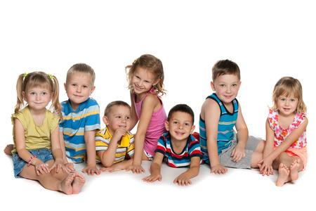 Zeven kinderen liggen en zitten op de vloer op een witte achtergrond