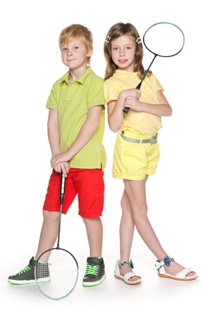 Two cheerful children a standing together and hold badminton racket photo