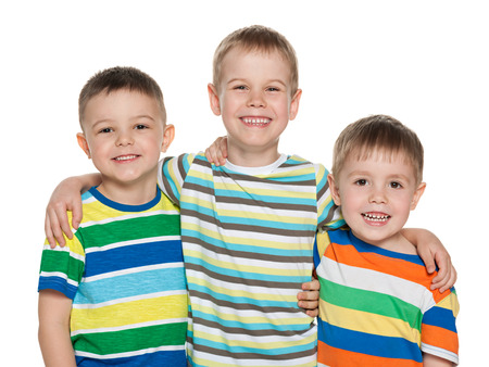 Three fashion joyful boys are standing together on the white background photo