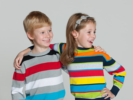 Two cheerful children are standing together on the grey background photo