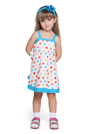 Portrait of a pretty little girl in polka dot dress on the white background