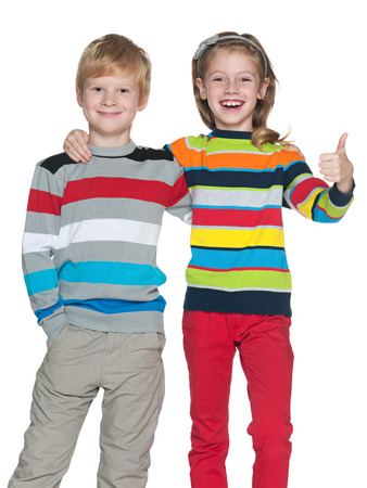 Two joyful children are standing on the white background photo