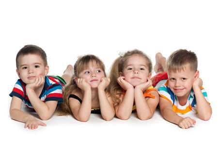 preescolar: Cuatro ni�os en edad preescolar son tumbado en el suelo en el fondo blanco