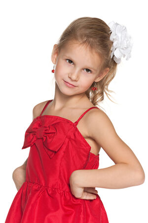 A portrait of a cheerful young girl in a fashion red dress on the white background photo