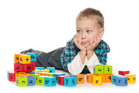 A pensive preschool boy is playing with blocks on the floor photo
