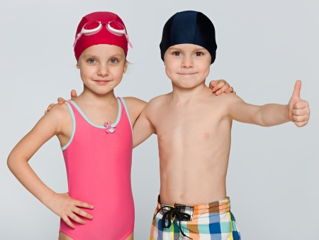 Portrait of two children in swimsuits on the grey background photo