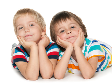 Two little boys are lying together on the white background photo