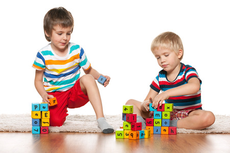 Two clever boys are playing with blocks on the floor photo