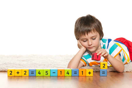 A pensive clever boy is playing with blocks on the white carpet photo