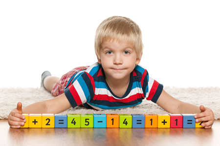 blonde boy: A blond preschool boy is playing with blocks on the floor