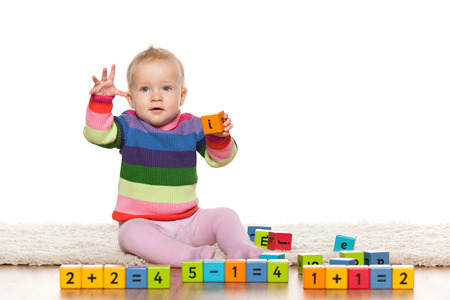 abc blocks: A baby girl is playing with blocks with digits on the floor Stock Photo