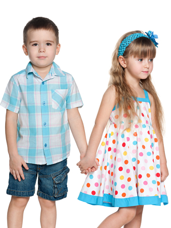 brothers and sisters: Portrait of two fashion children which standing together on the white background