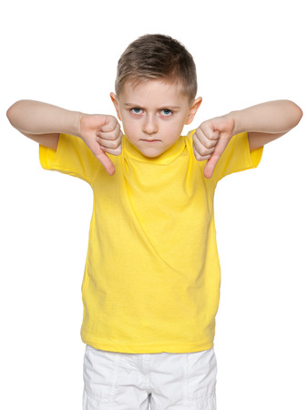 An upset boy in yellow shirt holds his thumbs down photo