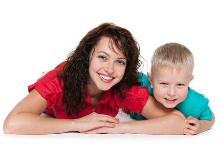 Happy mother with her son lie on the floor on the white background photo