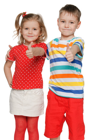 Portrait of a twor cheerful children hold his thumbs up on the white background Stock Photo