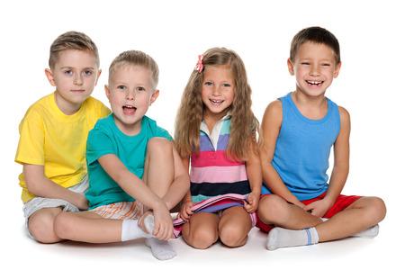 Een portret van vier lachende kinderen zitten op de witte achtergrond Stockfoto