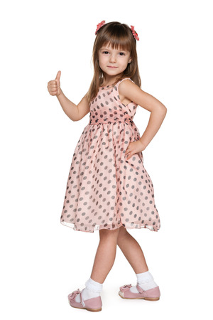 A walking little girl in a polka dot dress is holding her thumb up photo