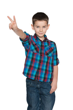 A portrait of a fashion little boy shows victory sign on the white background photo