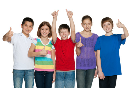 thumbs up group: A group of five happy children hold their thumbs up on the white background