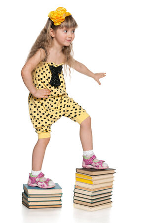 A cute little girl is climbing up the book stairs on the white background photo
