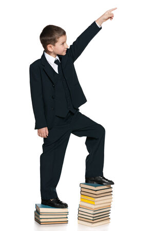 A cute schoolboy is climbing up the book stairs on the white background