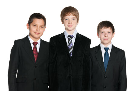 A portrait of three handsome young boys in black suits on the white background photo
