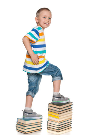 A cute little boy is climbing up the book stairs on the white