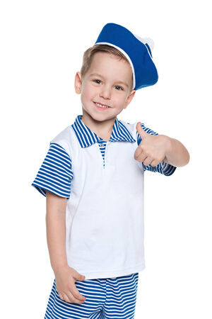 A portrait of a little boy in a sailor suit holding his thumb up on the white  photo